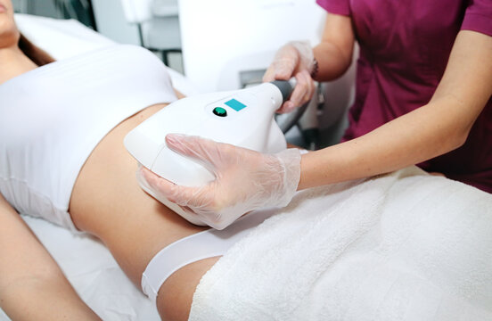 Young attractive woman in white bikini getting Cool sculpting procedure for body slimming. Cryolipolyse and body contouring treatment, anti-cellulite and anti-fat therapy in beauty salon