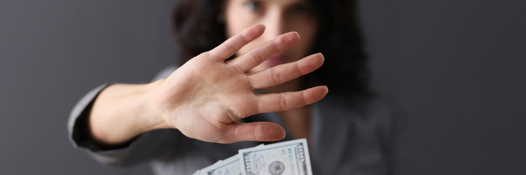 Business woman with hand refusing offered money closeup