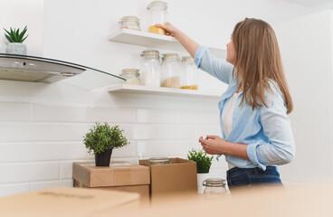 Fototapeta Woman arranges kitchen utensils after moving to new apartment. obraz