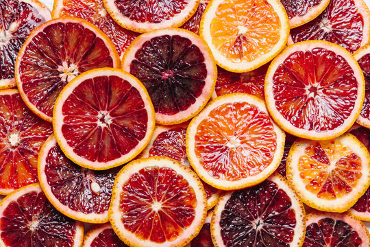 Bright colorful background of fresh ripe sliced blood oranges. Close up, flat lay. Orange texure, top view