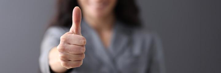 Fototapeta Modern business woman showing thumb up in office closeup