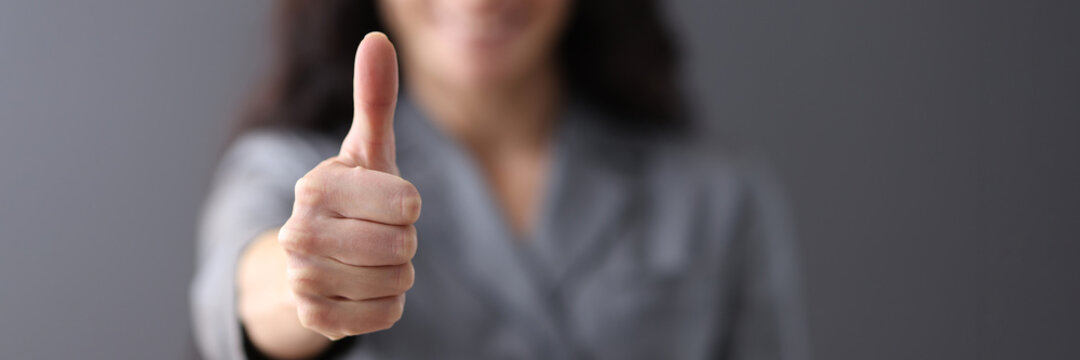 Modern business woman showing thumb up in office closeup