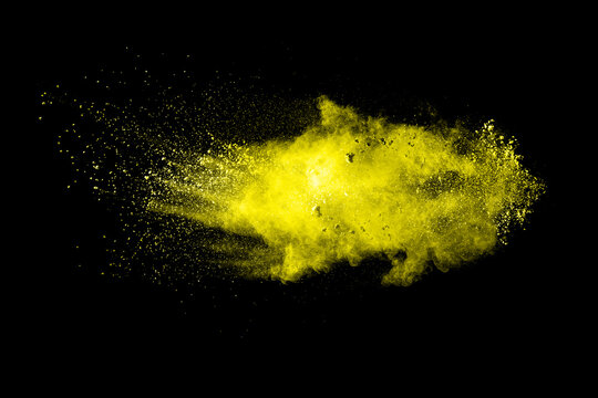 Abstract yellow color powder explosion on black background