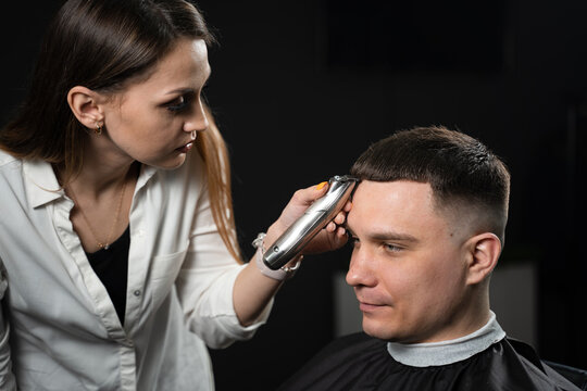 Trimming bangs of handsome man in barbershop. Woman hairdresser making hair style.