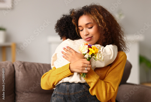 Young mixed race woman mother with flower bouquet embracing son while getting congratulations on Mother's day