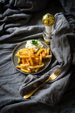 French fries with mayonnaise on grey plate and grey background- golden fork and salter.