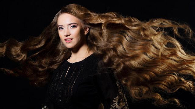 Attractive blonde with very long hair, wavy hair flying in the wind,