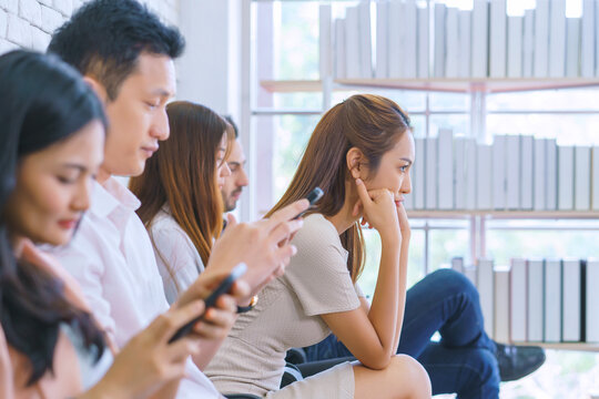 Beautiful young business women bored with other people all staring into their smartphones or cellphone. Concept of students addiction to social network and telephone technology