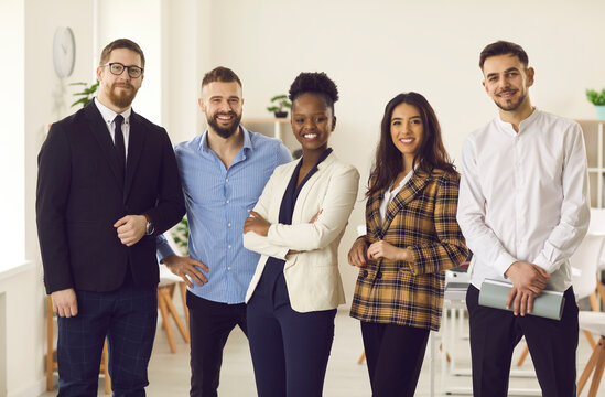 Group of five millennial people in office suits smiling and looking at camera. Portrait of confident young black businesswoman and company executive with team of happy employees. Female leader concept