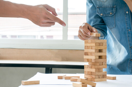 Group of Friends playing blocks wood gameon the table folded puzzle holding blocks wood game Planning risk and strategy in business concept
