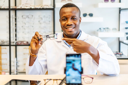 African american attractive optician entrepreneur is vlogger or Blogger show fashion glasses to cellphone and smiling selling it online live streaming in eyeglasses shop