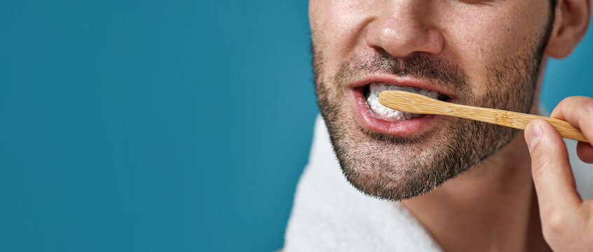 Cropped shot of man with towel around his neck brushing his teeth isolated over blue background