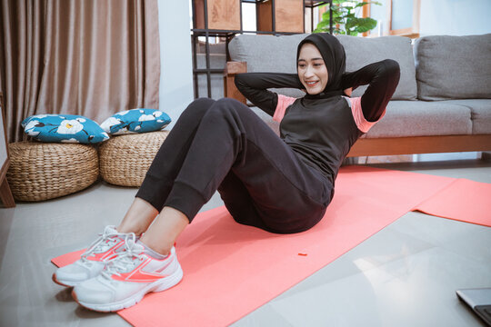 a woman in a hijab sport clothes doing sit ups to train her abdominal muscles while on the move at home