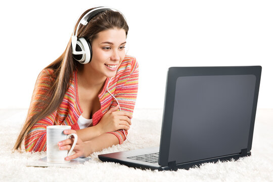 Smiling Woman use Laptop in Headphone. Young Girl work on Computer at Home. Happy Student Study in Earphone lying down and looking at Notebook Screen over White Background