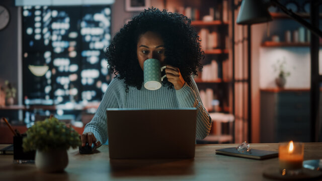 Beautiful Authentic Latina Female Sitting at a Desk in a Cozy Dark Living Room in the Evening and Using Laptop Computer at Home. She's Drinking from a Cup and Browsing Internet and Social Networks.