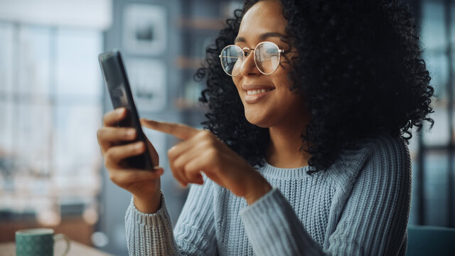 Portrait of a Beautiful Authentic Latina Female with Afro Hair in Stylish Cozy Living Room Using Smartphone at Home. She's Browsing the Internet and Checking Videos on Social Networks and Having Fun.