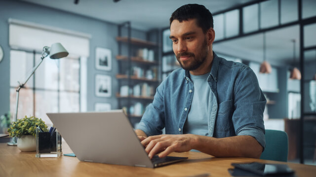 Handsome Caucasian Man Working on Laptop Computer while Sitting on a Sofa Couch in Stylish Cozy Living Room. Freelancer Working From Home. Browsing Internet, Using Social Networks, Having Fun.