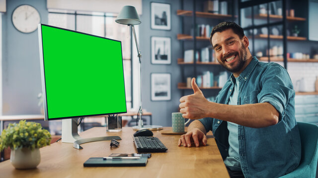Handsome Caucasian Specialist Working on Desktop Computer with Green Screen Mock Up Display at Home Living Room. Happy Freelance Man Smiles to the Camera and Shows a Thumbs Up Hand Gesture.