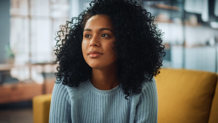 Portrait of a Beautiful Authentic Latina Female with Afro Hair Wearing Light Blue Jumper and Glasses. She Looks Away and Thinking about Life. Successful Woman Resting in Bright Living Room.