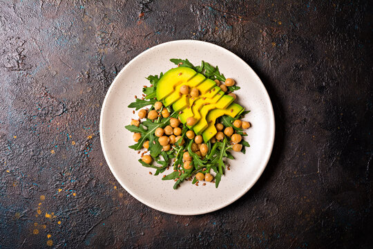 Healthy vegetarian food: cooked chickpeas with fresh arugula and avocado