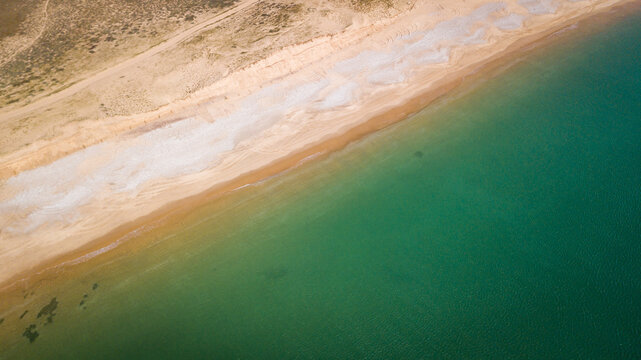 Aerial photography of sunny beach with part sand and part stones from above with clear water with a diagonale composition
