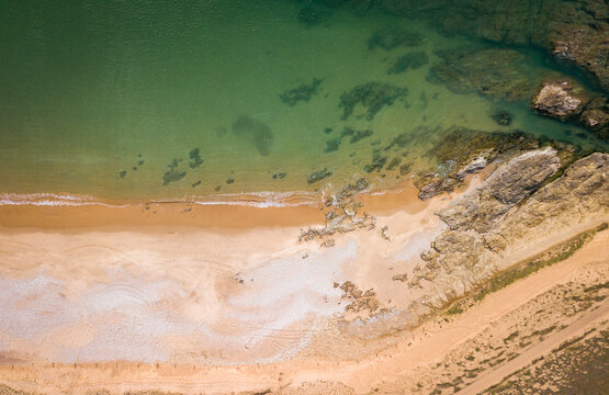 Aerial photography of sunny beach and rocks from above with clear water