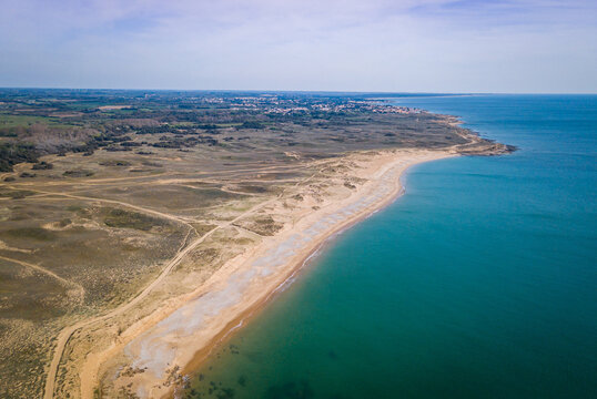 Aerial photography of sunny beach from above with clear water, sandy dunes behind and a small village in the background
