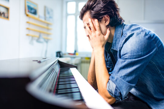 upset caucasian handsome musician man discontent singing, and teaching to play on piano