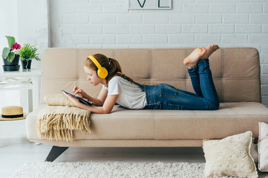 Red-haired girl child lying on the couch with an electronic tablet listens to music in yellow headphones. Remote learning, teenager using wireless devices doing homework or watching social networks.