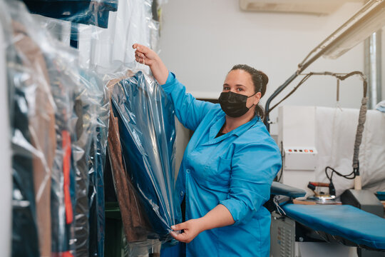 Woman in her 30s looking at the camera and placing the suit jacket that she has ironed on a hanger where she keeps the other clothes until the clients pick them up