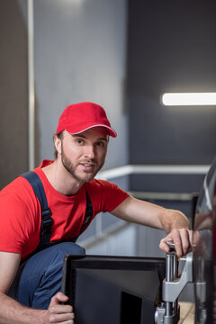 Experienced car service worker with wheel alignment stand