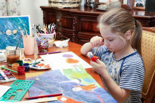 Preschool girl paints and makes papier mache crafts