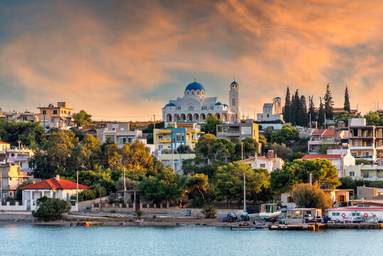 Salamis Island, Attica, Greece. The Assumption of Virgin Mary holy church in Salamis island, as seen from the ferry boat (route Piraeus - Salamis). Sunset, colorful cloudy sky