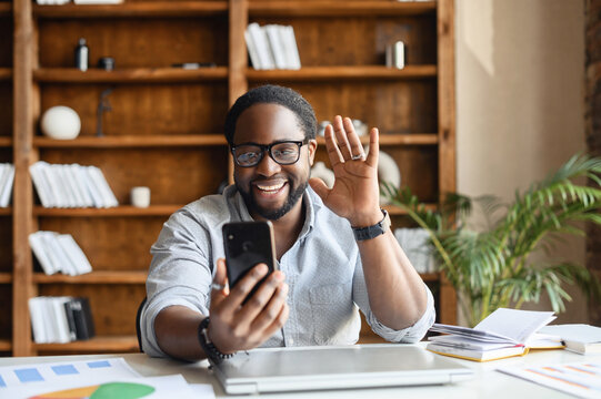Overjoyed African-American guy using a smartphone for video call sitting at the office, a mixed-race cheerful young man waving hi, glad to meet interlocutor, video meeting, virtual conference concept