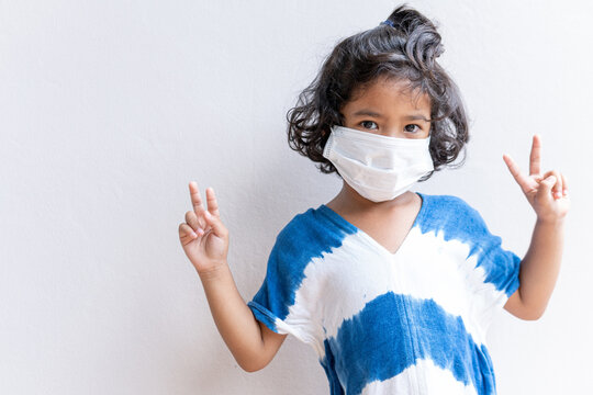 Close-up portrait of Asian Little girl  showing v-sign having fun wear white medical mask covid quarantine .selective focus