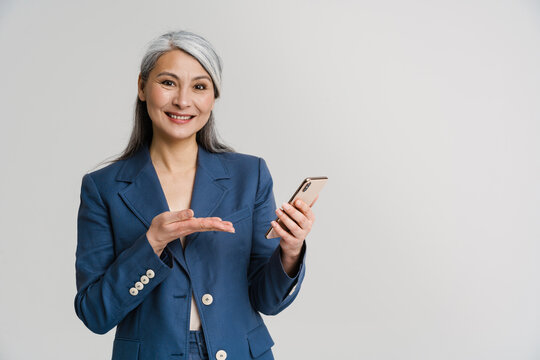 Asian mature woman smiling while pointing hand at her mobile phone