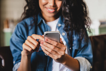 Obraz Cropped shot of an african-american young woman using smart phone at home. Smiling african american woman using smartphone at home, messaging or browsing social networks while relaxing on couch - fototapety do salonu