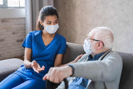 Doctor or female caregiver with senior man grandfather wearing protective mask to protect from Covid 19 at home or nursing home. Doctor talking consulting elderly patient at home