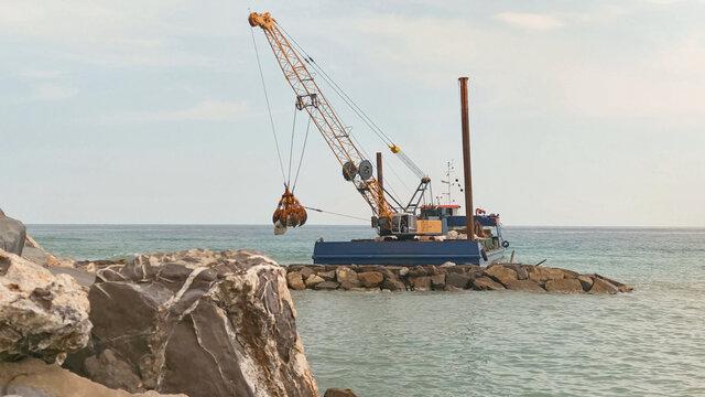 naval crane rebuilds a cliff