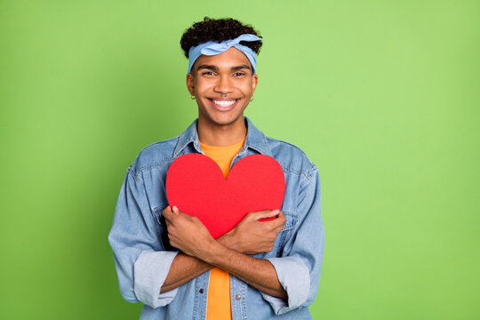 Photo of guy embrace big red paper heart wear earrings headband jeans shirt isolated green color background
