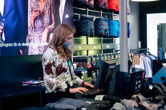 Female clothing store employee  wearing a mask