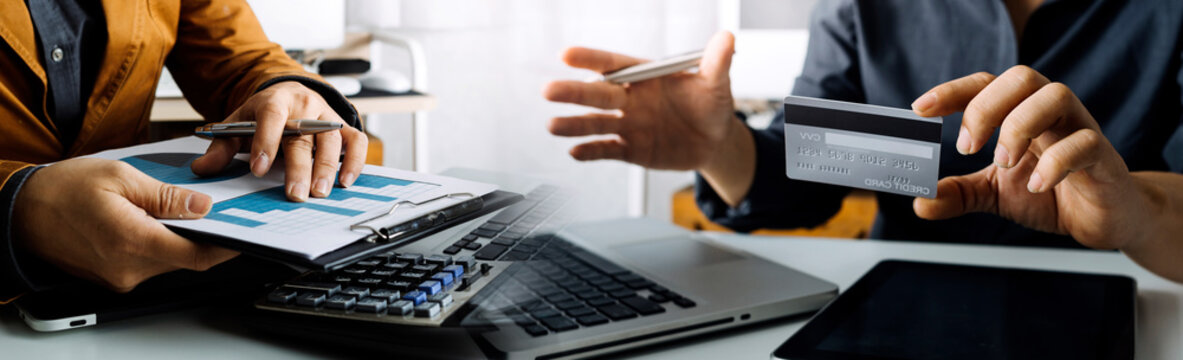 Business people use tablets and hold credit cards as an online shopping concept With a calculator and a book placed on the table
