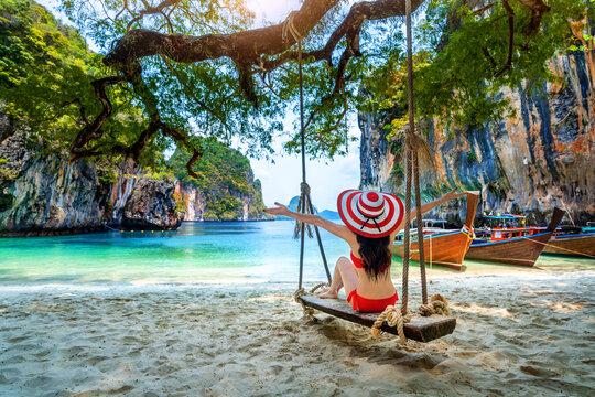 Woman in bikini relaxing on swing at Ko lao lading island, Krabi, Thailand.