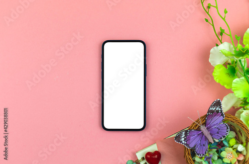Mother's Day mockup concept with blank white screen, modern workspace background with flowers and butterfly, top view