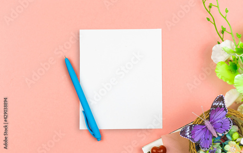 Mother's Day greeting card mockup concept with blank white paper and pen, spring composition with flowers and butterfly, flat lay and top view