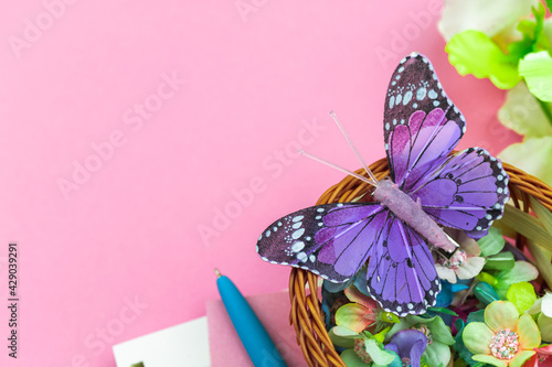 Spring and holiday workspace, pink background with flowers and butterfly, concept of mother's day greeting card