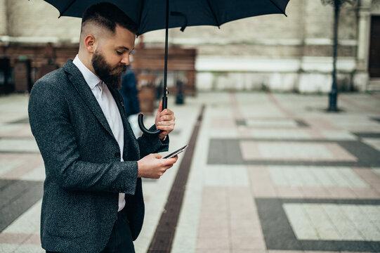 Businessman using a smartphone and holding a black umbrella