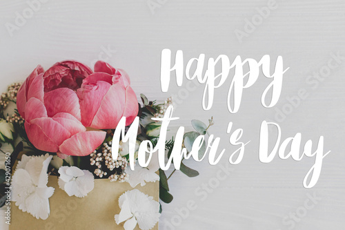 Happy mother's day. Happy mother's day text and peony,  flowers, eucalyptus growing from envelope on white wood. Stylish floral greeting card. Handwritten lettering. Mothers day