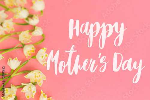 Happy mother's day. Happy mother's day text and spring flowers border on pink paper. Stylish floral greeting card. Handwritten lettering on white spring snowflakes on pink. Mothers day