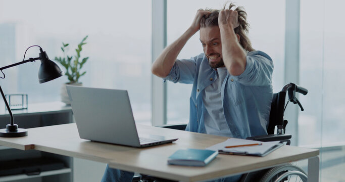 Depressed angry young man office worker losing computer data having problem internet connection screaming inside office corporate space. Emotions. Disabled person.